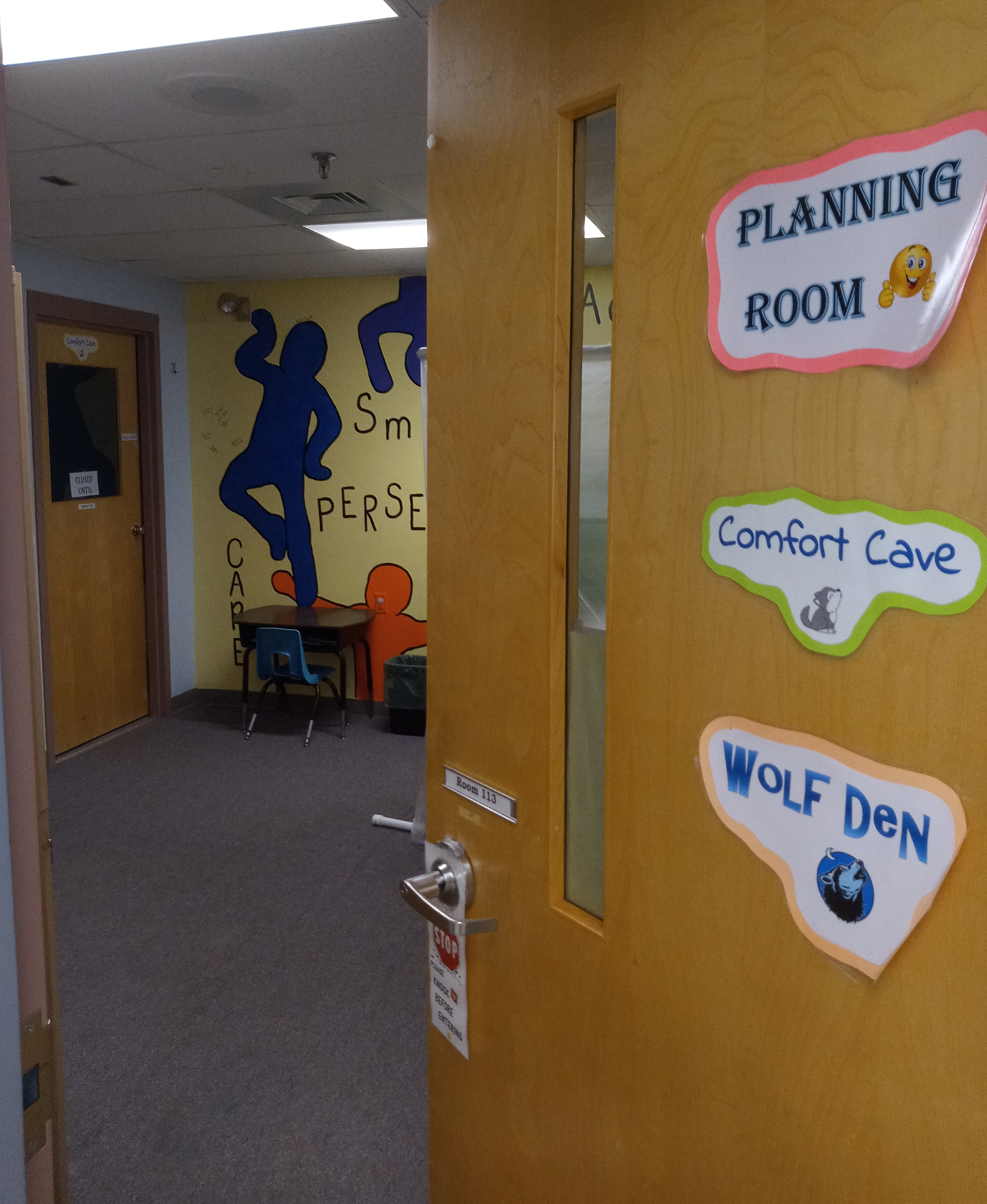 Photo of the door to the planning room with inviting signs on it.